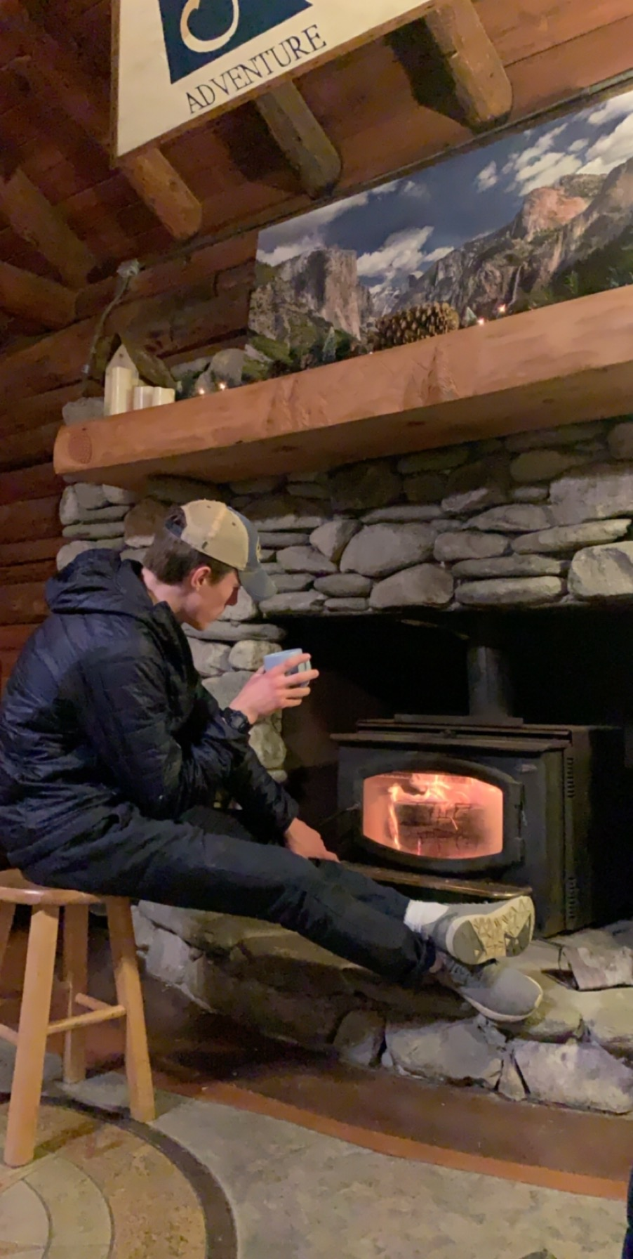 Student by wood stove at Summit Adventure base in California