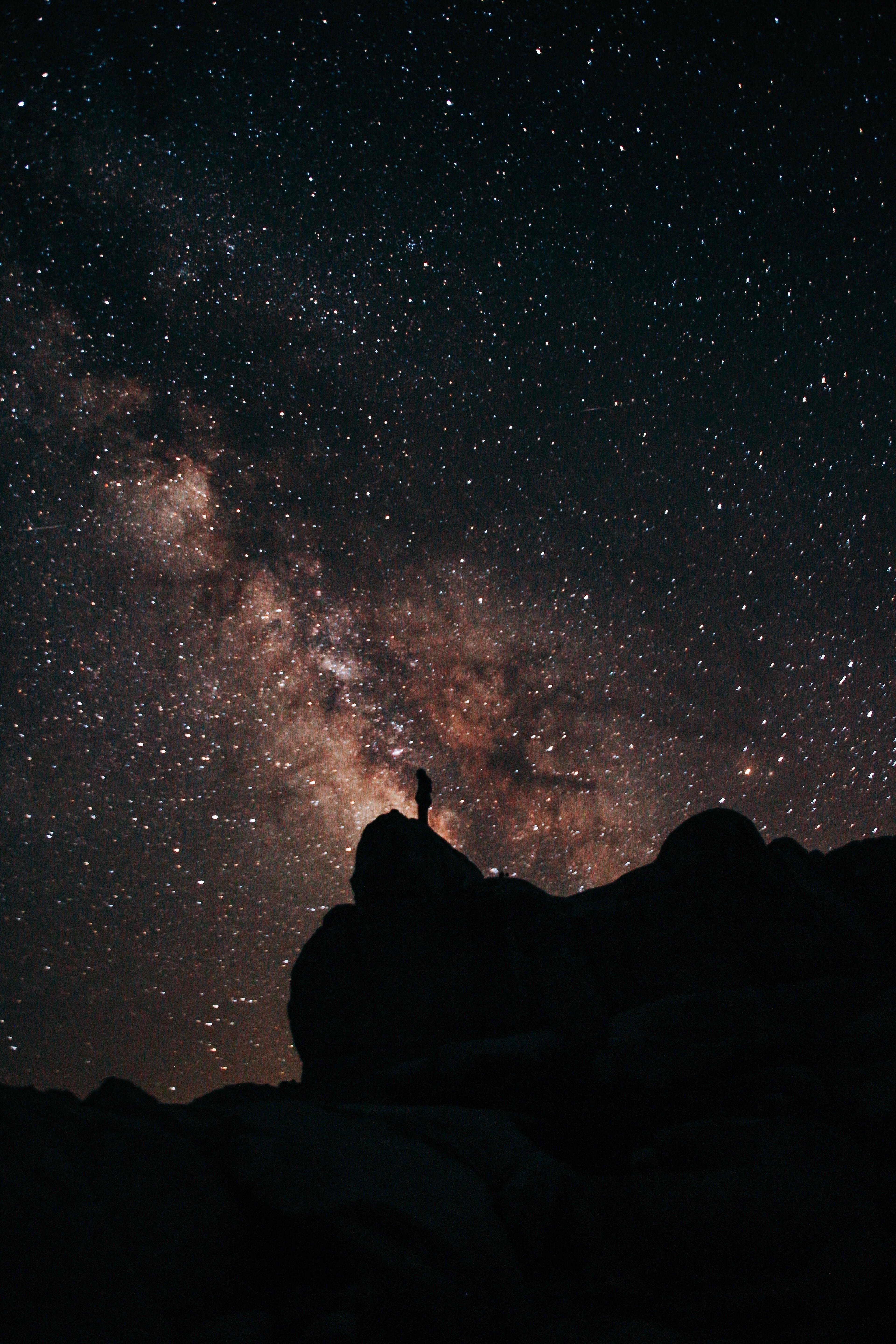 A picture of a person standing under the Milky Way at night milky way galaxy star shot wilderness